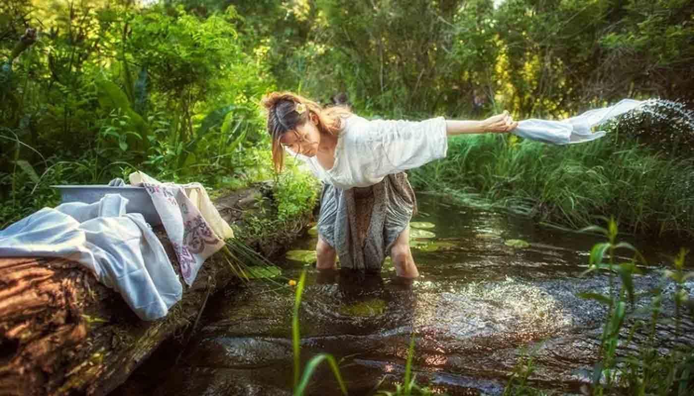 Женщина стирает бельё в водоеме и купается спасаясь от жары